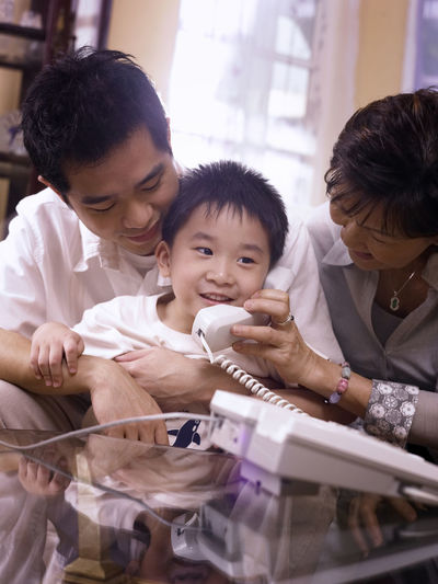 Smiling boy talking on landline phone while sitting with grandmother and father at home