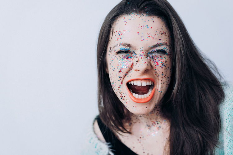 Close-Up Portrait Of Young Woman With Confetti Against Wall