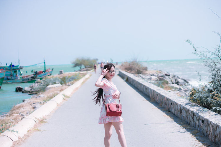 Portrait of woman wearing eyeglasses standing on footpath against sea and sky
