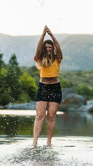 Full length portrait of woman splashing water while standing in lake