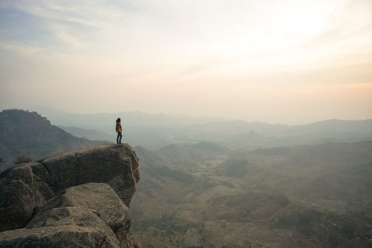 Man standing against mountains on cliff during sunset