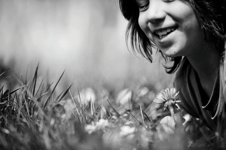 Close-up of boy with flowers in field