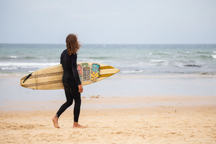 Rear view of woman with surfboard on beach