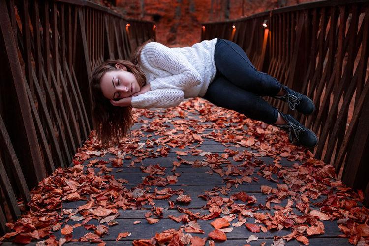 Woman Sleeping While Levitating Over Autumn Leaves Covered Footbridge