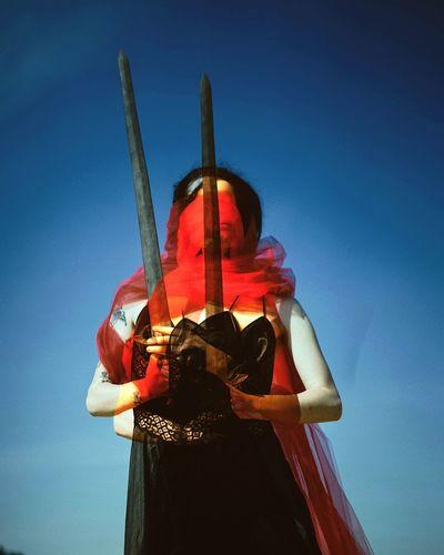 Man holding red umbrella against blue sky