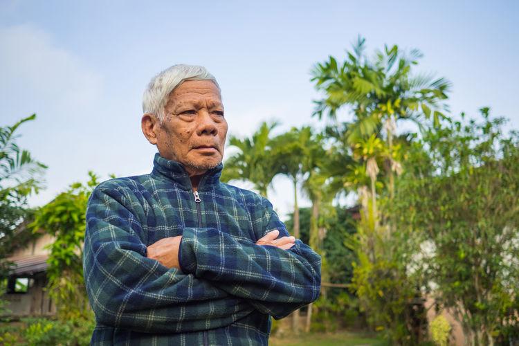 Portrait of elderly man standing and arm crossed in garden