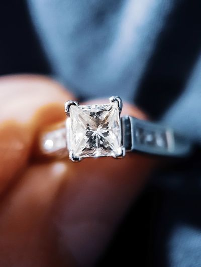Close-up of human hand holding diamond ring