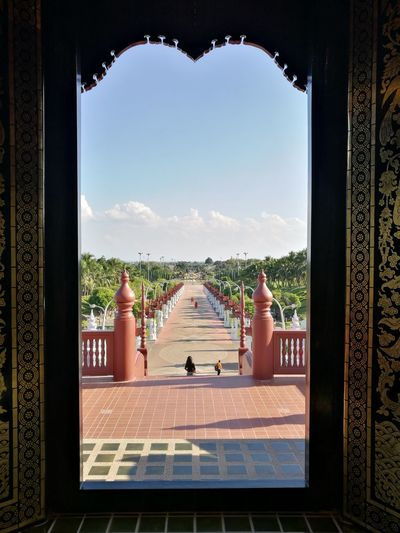Pathway seen through ornate entrance on sunny day