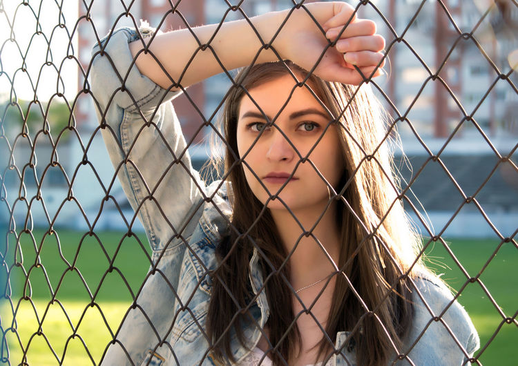 Portrait Of Young Woman Leaning On Chainklink Fence At Court