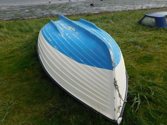 A small colourful boat on the beautiful magical and mystical island of Lindisfarne (The Holy Island) of the coast of Northumberland, England. Colourful Derelict Blue Boat Day Field Grass High Angle View Landscape Lindisfarne Nature No People Outdoors Upturned Boat Water