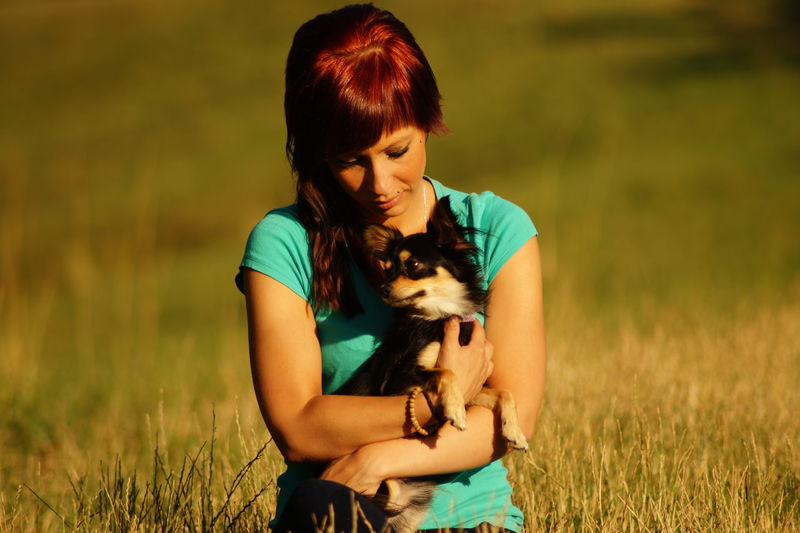 Young woman with puppy sitting on grassy field