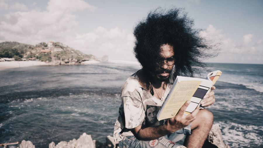 Man sitting on book by sea against sky