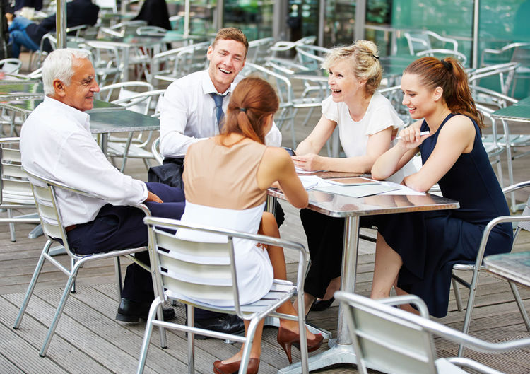 Business Colleagues Discussing While Sitting At Outdoor Cafe