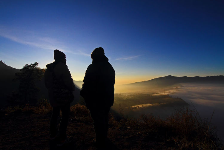 Rear view of silhouette couple standing on mountain at sunset