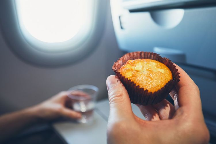 Close-Up Of Hand Holding Cupcake In Airplane