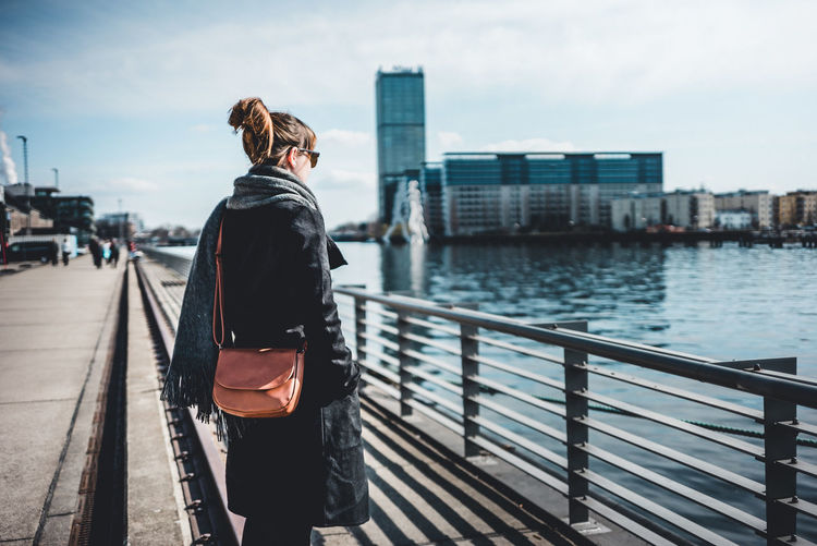 Rear view of woman on bridge against cityscape