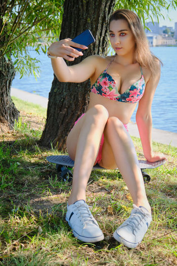 Beautiful young woman using mobile phone while sitting on land