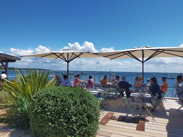 People relaxing on table by sea against sky