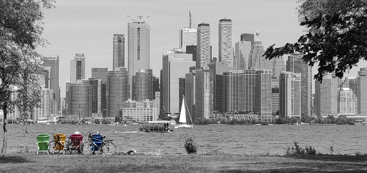 PEOPLE IN PARK BY MODERN BUILDINGS AGAINST SKY