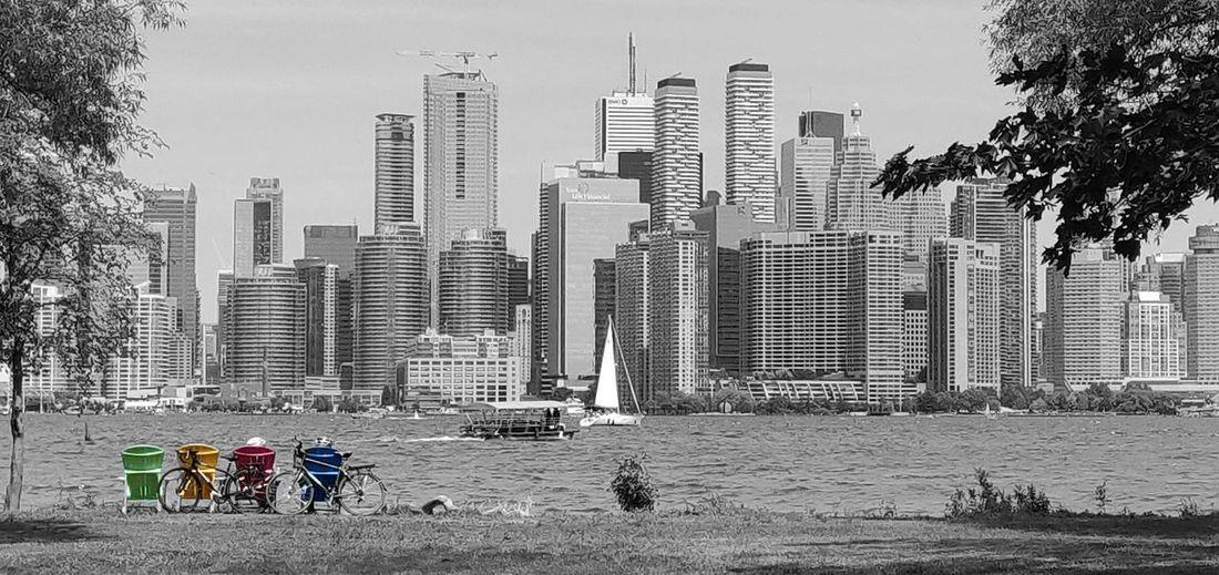 People by modern buildings in city against sky