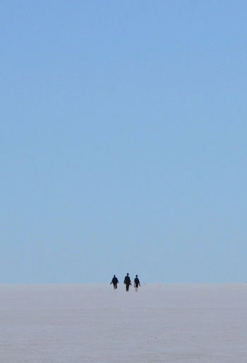 View of two silhouette people on landscape against clear sky