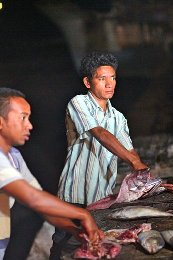 Men cutting fish on stall at market for sale at night