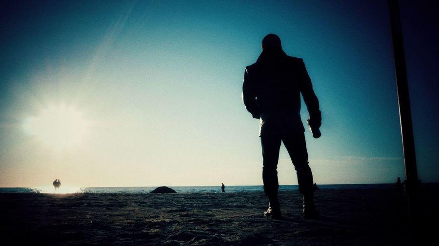 Silhouette men standing on beach against sky during sunset