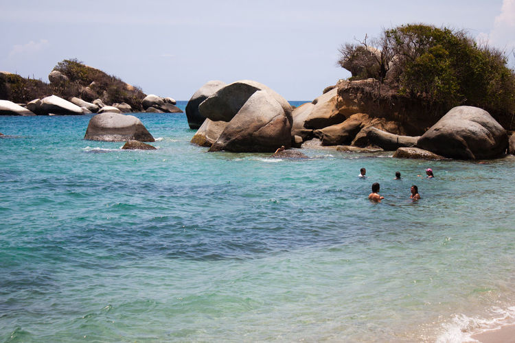 People Swimming In Sea By Rocks