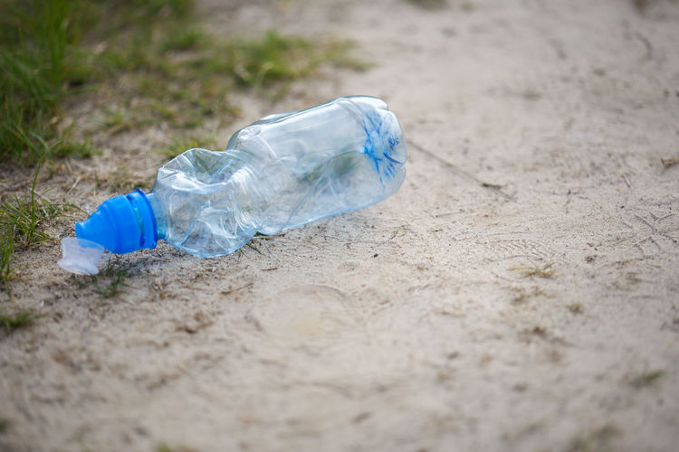 Close-up of water bottle on sand