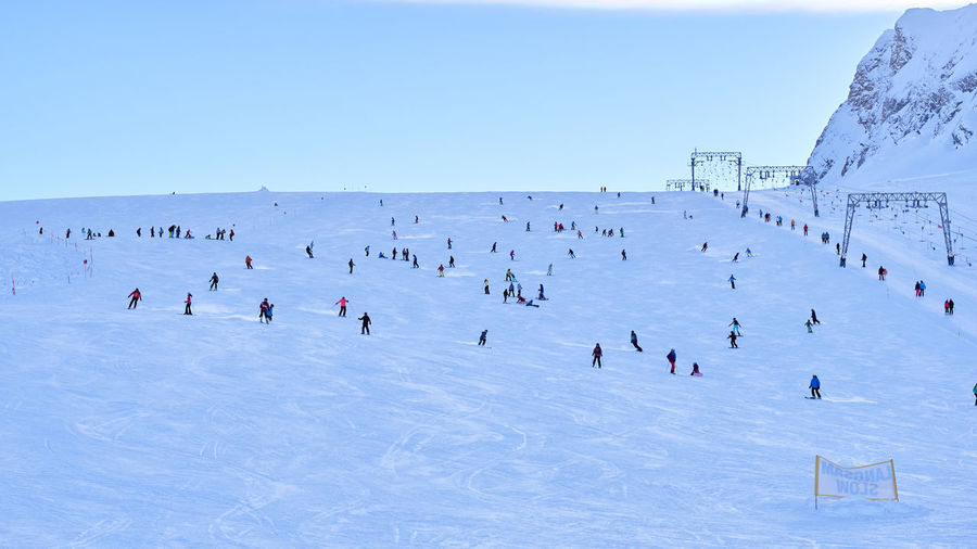 People Skiing On Snow Covered Landscape During Winter
