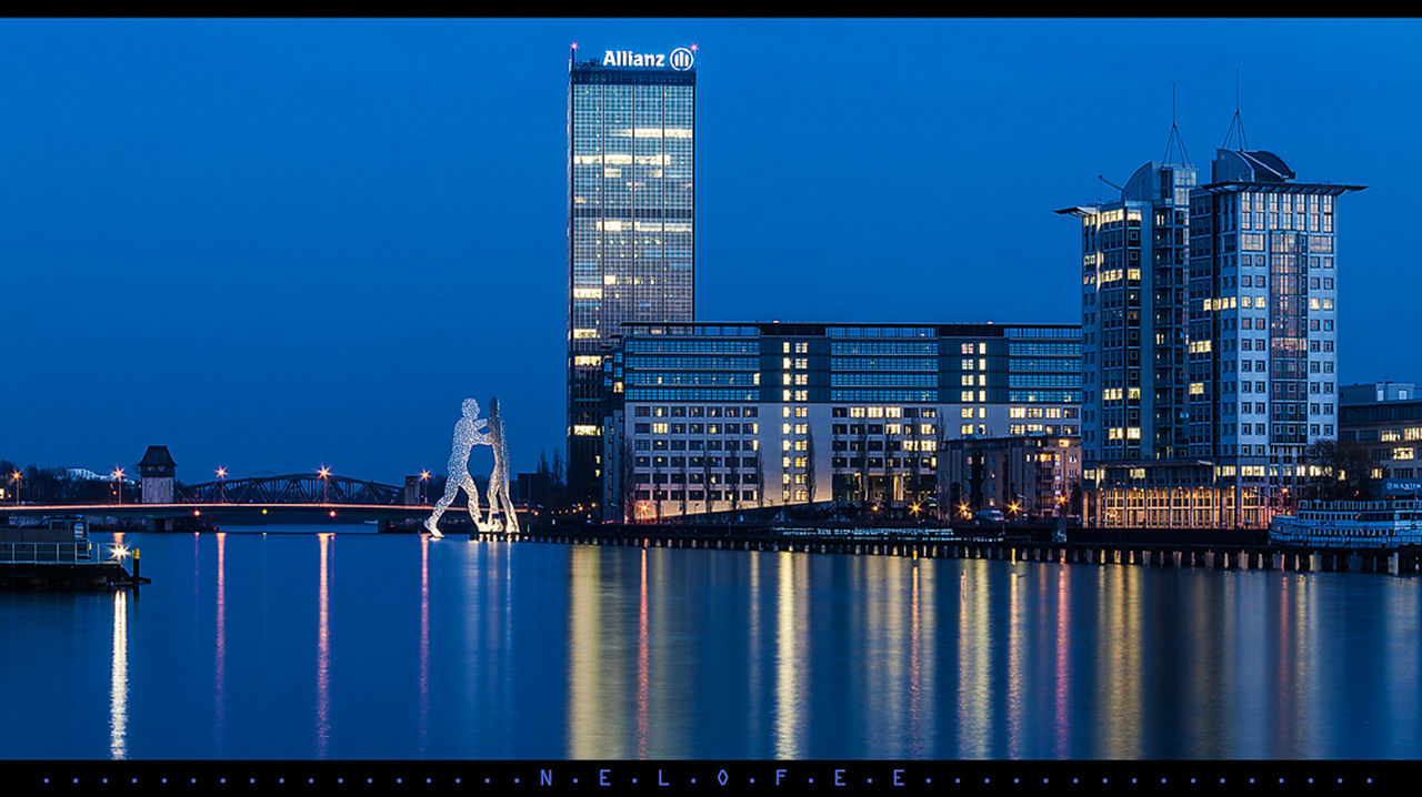 architecture, building exterior, illuminated, built structure, skyscraper, city, night, waterfront, clear sky, river, travel destinations, outdoors, modern, cityscape, blue, urban skyline, water, sky, no people, nautical vessel