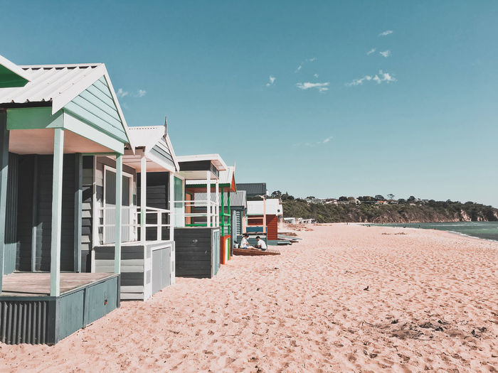 Beach huts against clear blue sky in melbourne