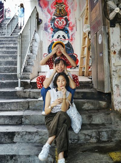 Portrait of women sitting on staircase at temple
