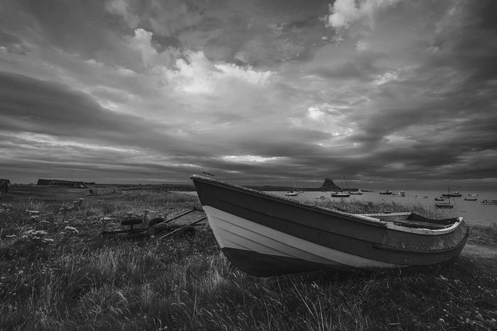 Grounded By The Sea Cloudporn Skyporn Cloud - Sky Rowboat Monochrome Coast Northumberland Lindisfarne Nautical Vessel Mode Of Transport Transportation Boat Cloud - Sky Sky Outdoors No People Scenics Beauty In Nature Moored Tranquility Landscape