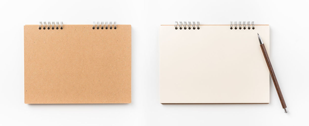 Directly above shot of spiral notebooks against white background