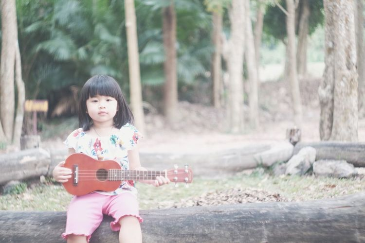 Portrait of girl playing ukulele while sitting at park