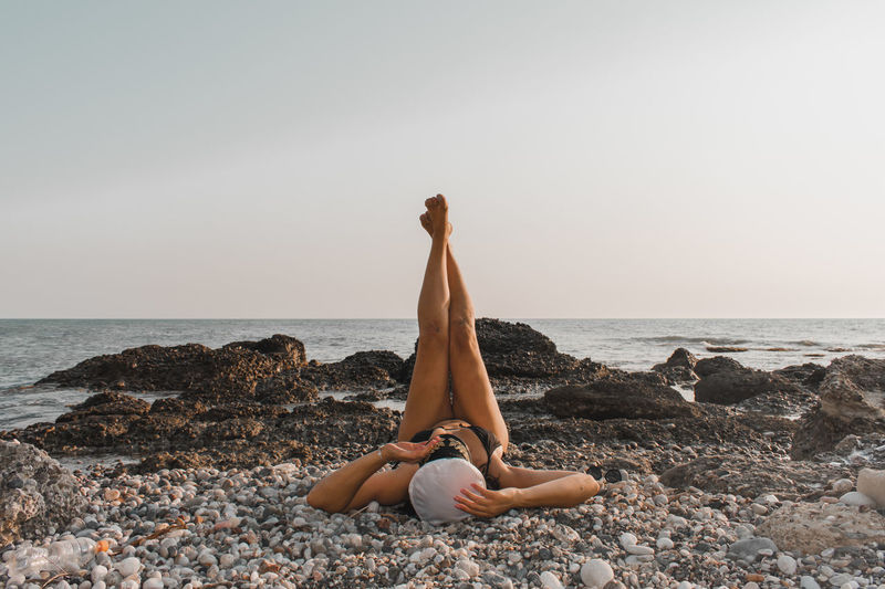 Woman relaxing on rock at beach against sky