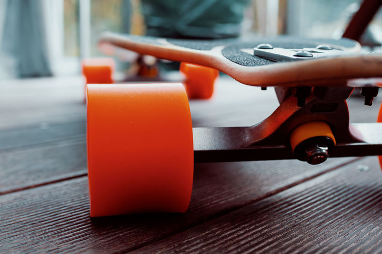 FOR FUN Skateboarding Skateboard No People Close-up Wood - Material Orange Color Safety Equipment Still Life Security Metal Wheels Focus On Foreground Table Indoors  Day Red Selective Focus Absence Plastic Food And Drink Technology