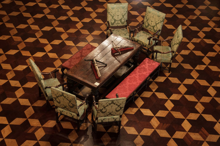 High angle view of chairs and tables arranged on tiled floor