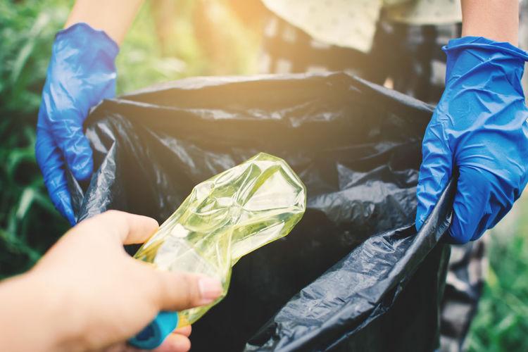 Cropped Image Of Hand Throwing Plastic Bottle In Garbage Bag Held By Volunteer