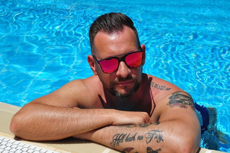 High angle view of shirtless mature man wearing sunglasses relaxing at poolside during sunny day