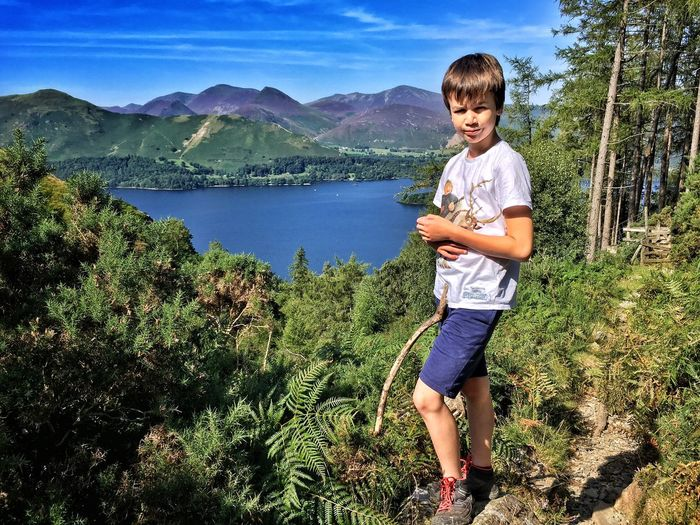Full length portrait of boy standing by derwent water and mountains against sky