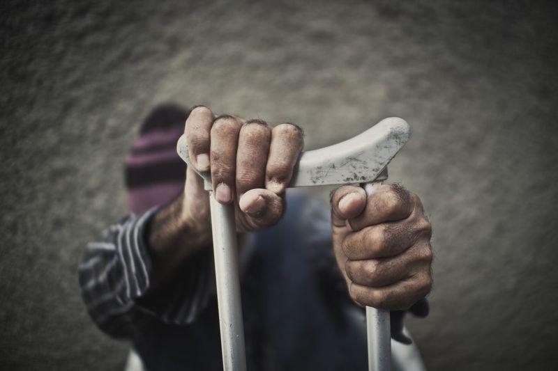 Man Holding Crutch Against Wall
