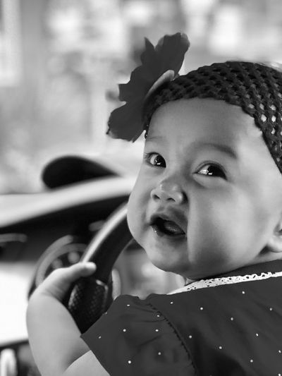 Close-up of cute baby girl holding steering wheel in car