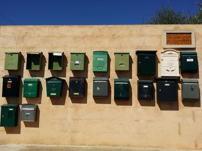 Low angle view of metallic letterboxes on wall