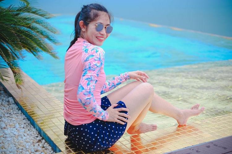 Woman wearing sunglasses sitting on swimming pool