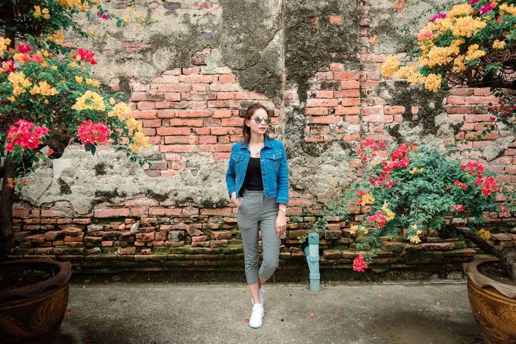Woman In Sunglasses Standing Amidst Flowering Plants Against Brick Wall