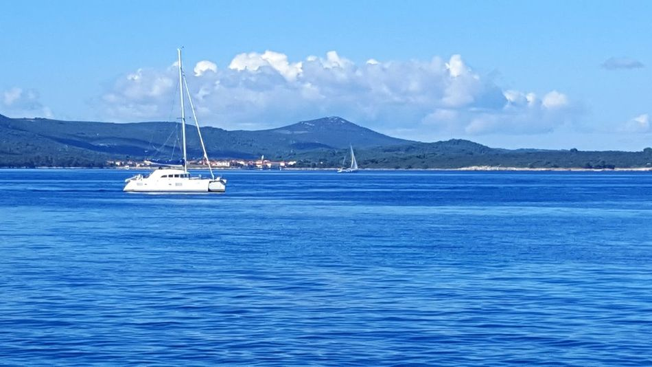 Blue Nautical Vessel Sea Outdoors Water Horizontal Sailboat Day Sailing No People Mountain Beauty In Nature Sky Yachting Cloud - Sky Beauty In Nature Sunny Clear Sky Cityscape