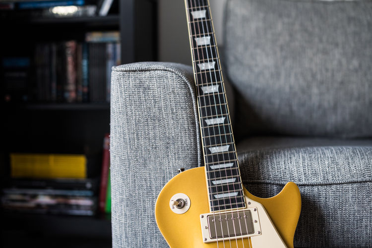 Close-up of guitar by sofa at home