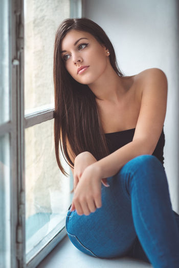 Thoughtful young woman looking through window while sitting at home